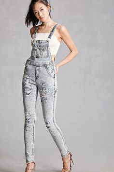 A pair of acid wash denim overalls featuring a skinny fit, distressed design, adjustable straps, button sides, front bib patch pocket with four slits, a five-pocket construction, and a faux fly. This is an independent brand and not a Forever 21 branded item.