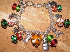 Artisan Handcrafted Silver Christmas Charm Bracelet with Rudolph the Red Nosed Reindeer, Christmas Ornaments, Handmade Lampwork Glass Beads, and Christmas Themed Pewter Charms. Handcrafted by MelancholyMind on Etsy