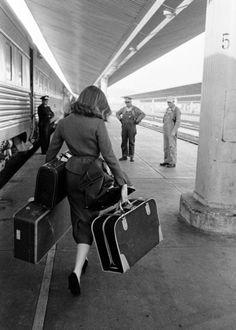 A woman disembarking a train, 1950s. Photo by Allan Grant.