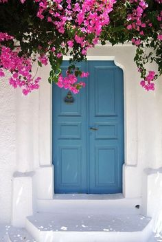 blue door with white walls and bougainvillea