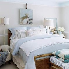 Layers of sky blue and white bedding lend this guest room a warm and welcoming air. A lightly ruffled bed skirt and the scalloped edges of a blanket introduce a simple sweetness that's echoed by silk lampshades and a dreamy sheep rendered in oil paints above the bed./