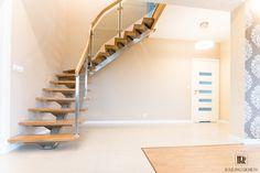 Nowoczesne schody ażurowe,  z drewna dębowego na konstrukcji nierdzewnej. Balustrada nawiązująca do schodów, wykonana z nierdzewnych profili wypełnionych dymioną szybą klejoną, zwieńczoną drewnianym pochwytem.