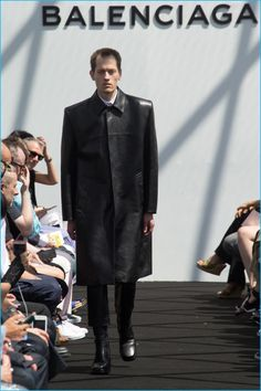 Balenciaga has a minimal moment with a long and wide black leather coat.