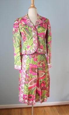 Vintage 1960s Emilio Pucci skirt suit in 100% pure silk. Amazing abstract floral design in shades of green, pink, taupe and cream. Classic 60s silhouette. Hidden snap button closure down the front of the jacket. Skirt is a line and pleated. A very desirable piece to wear and collect! Jacket Bust-33 Waist-32 Length-20  Skirt- Waist-26.5 Length-27.75  The fit is very tailored. This would best fit a size 4 to a small size 6. Condition- Excellent