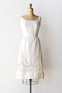 "Vintage 1960s white dress made from heavier knit cotton with jacquard design. Scoop neckline, sleeveless seamed bodice, and low back. Scalloped and garlanded along the hem in soutache, sheer lace and embroidery. | 34"" bust x 25"" waist x 38"" hips (Waist might be a bit tight!) 