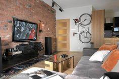PO ZMIANIE. Pokój umeblowano na nowo. Narożna kanapa jest większa od poprzedniej. Szklany blat stolika, zrobionego na zamówienie, wspiera się na podstawie z wyciętych ze sklejki liter układających się w wyraz Bike (rower). Nietypową ozdobą jest zawieszony na uchwytach rower.
