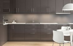 Cozinha moderna em cinzento brilhante da IKEA com bancadas claras e eletrodomésticos integrados.