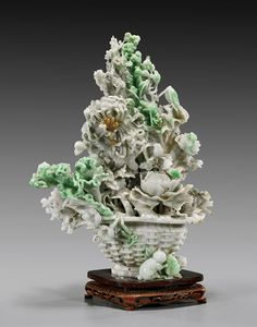 """Elaborately carved in full openwork, Chinese jadeite group; of a flower basket overflowing with auspicious flowers including chrysanthemums, peonies, plum, pomegranates and a citron to the verso, with crickets hidden amid the foliage and two small cats with gourd plaque to the front base; the stone of white and pale green coloration with bright apple green suffusions; H: 14""""; carved wood stand;"""