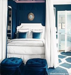 Love this dark, peacock blue bedroom. Looks great with gold wall decor, white curtains (and bedspread) and dark blue pillows.