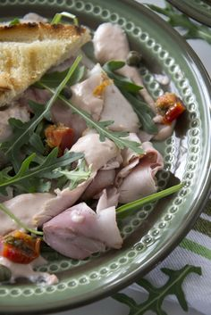 Vitello tonnato geserveerd met rucola, en stokbrood.