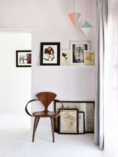 Detail from master bedroom.   Vintage Norman Cherner chair.  Artwork by Sid, vintage maps and illustrations by Rebecca's friend James Daw.  Photo – Eve Wilson, production – Lucy Feagins / The Design Files.