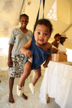 A baby is weighed in a sling-scale at a UNICEF-supported baby-friendly tent in Cité L'Eternel, a slum in Port-au-Prince, Haiti. Baby-friendly spaces offer nutrition counselling, food and medicine, and a safe place for mothers to breastfeed.      © UNICEF/Roger LeMoyne    http://www.unicef.org