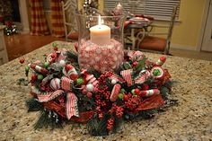 The base is a small wreath and everything is secured with the greenery. The candle holder is full of real peppermints