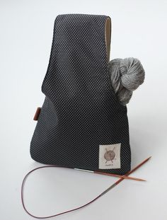 A black with tiny white polka dots project bag. The easy way to knit... You put that bag on your wrist whit the yarn inside and it rolls out while you work. Its perfect to knit anywhere, in a car, a waiting room, standing up while waiting for the bus, name it! This wristlet is the small version, it mesures 12.5 tall X 8. It can handle only 1 yarn ball. Its a good size for knitting socks or small items (Its also available in medium) It is made of a light black and white cotton and inside a...