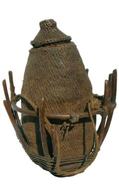 Africa | An antique Somalian water vessel woven from plant fiber. | it is contained in a frame made from twigs and laced with hide. This vessel would have been hung on the side of a camel while travelling in the desert