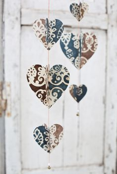 paper heart strings - okay- imagine these in brighter colors, but the heart is cut into concentric hearts. Then, when they are sewn thru the centers they open up into 3D hearts! So cool!