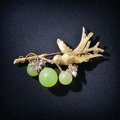 How cute is this? A golden bird is swooping down to sample some grapes made of life-like frosted green glass beads. Rose-cut diamond leaves add extra sparkle. Circa 1890.