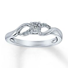 A round diamond takes center stage in this appealing ring for her.  Additional round diamonds dance on either side for added allure. This fine jewelry ring is styled in sterling silver. Diamond Total Carat Weight may range from .04 - .06 carats.