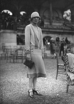 March 1925 ~ A woman wearing a day dress with a design inspired by maritime clothing, at the races.