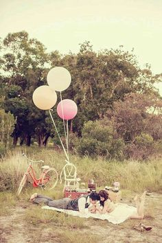 Cute picnic set-up with pastel-colored balloons and a vintage cruiser bike