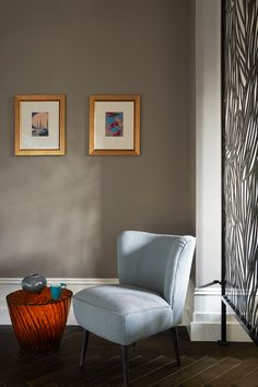 Dark walled Farrow and ball paint against this teal blue tub occasional chair. With orange glass side table and gold framed pictures on the wall. Herringbone chevron dark wood floor gives glamour to the space. The lattice screen divides the space. Picture Wall, Picture Frames, Lattice Screen, Farrow And Ball Paint, Edwardian House, Glass Side Tables, Dark Wood Floors, Occasional Chairs, Accent Chairs