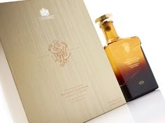 The box was crafted using complex rigid board construction, and is wrapped in bespoke paper stock, debossed with a fine wood grain effect. On the front of the case, the John Walker & Sons monogram is displayed in deep copper foil. Providing a striking contrast is the silver foil Royal Warrant emblem. The whisky bottle is held snugly in a fitted recess in the main body of the case, and can be easily slipped out with an attached copper ribbon. Opposite rests a hardback information booklet. Johnnie Walker Whisky, John Walker, Luxury Packaging, Wood Grain, Booklet, Bespoke, Scotland, Sons, Contrast