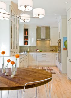 Simple accents. Accessorizing in a transitional kitchen is minimal — note the pared-down pottery collection and deconstructed floral arrangement in this space. Avoid fussy displays and clutter, and keep patterns simple and graphic.