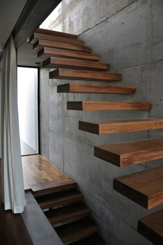 Floating timber stairs, concrete walls.