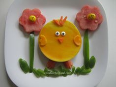 Baby Chick Creative Kid Easter Lunch ~The baby chick is an open faced ham and cheese sandwich cut w/circle cookie cutter.  *Use your favorite yellow cheese. *The chick's hair, beak and feet are carrots.   *The eyes are edible eye candies.   *The wings are made from the same cheese as the body. ~The flowers are watermelon cut with a flower cookie cutter with carrot centers. *add some green pepper stems, leafs and grass.  -And what is that in the flowers? A baby chick M on top of the carrot!