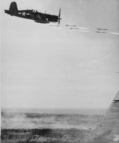 Corsair fighter looses its load of rocket projectiles on a run against a Jap stronghold on Okinawa. In the lower background is the smoke of battle as Marine units move in to follow up with a Sunday punch. Lt. David D. Duncan ca. June 1945.