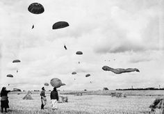 German women pause in their harvesting to watch the landing of paratroopers
