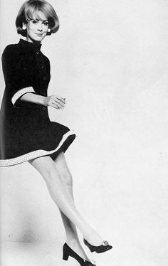 Catherine Deneuve in black silk dress with small standing collar, full sleeves with crisp white bands of lace by Yves Saint Laurent, photo by David Bailey for Vogue, 1967