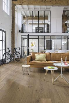 contemporary industrial loft with white brick walls and high ceilings   leather couch and hardwood floors   living room   residential interior design