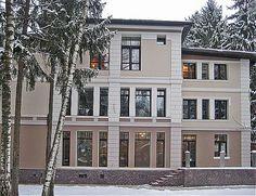 Классический фасад дома без основных ордерных элементов. Стиль подчеркивается белыми наличниками, фронтоном, обрамлением балкона.