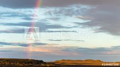 Stock Footage of A static timelapse of a rocky yet flat landscape with a breathtaking rainbow and scattered clouds gently moving through as the sun rises over the landscape. Explore similar videos at Adobe Stock Windmill, Geology, Stock Video, Stock Footage, South Africa, Adobe, Sunrise, African, Rainbow