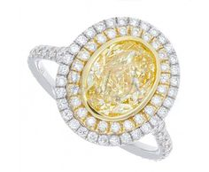 """This beautiful ring features a natural certified Fancy Light Yellow Oval Cut Diamond in the center surrounded by round brilliant cut diamonds continuing down the shank in a modern """" U """" shape pavé setting creating a setting that is simple and elegant."""