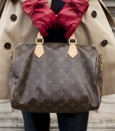 Louis Vuitton Speedy bag, red gloves, and a trench coat made for a polished pairing.