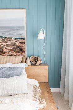coastal beach style bedroom with blue walls, wooden bed frame, large photo above bed, white sheers