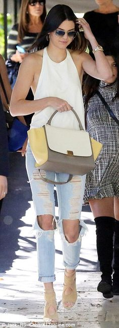 Nailed it! The leggy brunette was effortlessly chic in heavily distressed pale jeans wit gaping holes in the knees, tan suede cut-out stilettos and a white halterneck top that was cut low at the back, while she carried a white, grey and pale yellow designer handbag