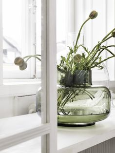 hand blown green glass vase with green pod arrangement