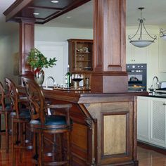 Repurpose Architectural Finds--A mahogany bar from an English pub finds a new home dividing this kitchen from its living area. Guests can sit at the bar and talk to the cook without even entering the kitchen.