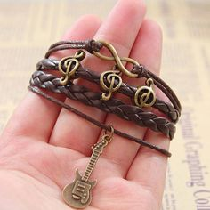 "Size:18CM(7"")+5CM(1.9"")extended+chain  Color:Coffee  Weight:+14g  Material:+braided+leather+cord+/Wax+rope/+Alloy+  Style:Retro  Fashion+Element:Happy+Notes/Guitar/Infinity+  Do+you+like+the+music?+Guitar+bracelet+is+your+necessary+accessories! The+Happy+Notes+Guitar+Infinity+Brace..."