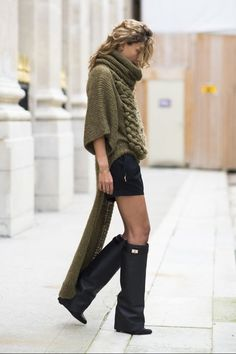 Givenchy boots- Ignore the boots.  Notice that sweater is cunningly designed to hide her tail.  Or maybe it's like what truckers have behind the wheels to keep down spray.  Is there an intarsia naked lady on it?  I can't see.