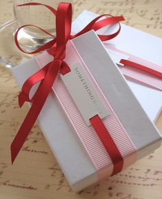 Elegant...Sometimes the most simple packaging can turn out to look even more luxurious then the more intricate ones. Tie 3″ grosgrain ribbon around a white box, then tie 5/8″ red satin ribbon around the white box with a tag in the middle.
