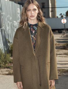 Model Sasha Pivovarova poses in Zara oversized coat and floral print dress