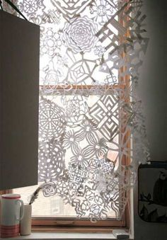 "Paper cut-outs of snowflakes create a visually striking Christmas ""curtain."" Cut out snowflakes in different shapes and sizes and tape or glue together."