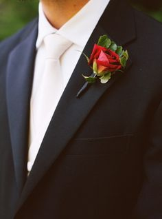 Very sophisticated wedding attire. Black suit, white shirt, white tie, Boutonniere that matches brides bouquet. Would also look great with a dark charcoal color suit.