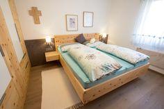 Modernes Zirbenschlafzimmer mit Zirbenbett in Schwebeoptik und Nachtkästchen in Schwebeoptik. Oberfläche geölt mit Zirbenöl, gefertigt in unserer Tischlerei in Gosau aus österreichischem Zirbenholz.
