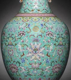 A famille rose turquoise-ground vase Daoguang seal mark and of the period Sold for £181,250 (US$ 240,770)  The ovoid body raised on a short foot and intricately enamelled with four fully blossoming stylised lotus amid scrollwork each beneath a gilt Buddhist wan symbol, alternating with a bat suspending a canopied ruyi-head tassel amid double-seeded lotus scrolls, all between stiff lappets at the foot and a band of ruyi heads at the shoulder, the neck enamelled on each side with a bat above a