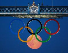 Perfectly timed photo of the full moon rising through the Olympic Rings hanging beneath Tower Bridge during the London 2012 Olympic Games August 3, 2012.  image credits: REUTERS/Luke MacGregor